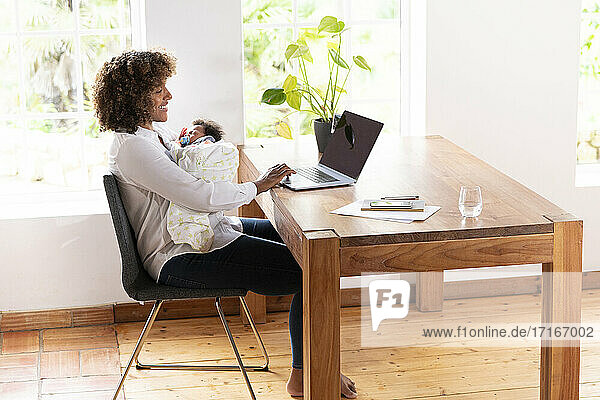 Mid adult woman holding baby while working on laptop at home