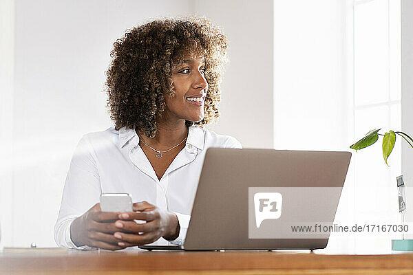 Lächelnde Geschäftsfrau mit Laptop und Mobiltelefon,  die wegschaut,  während sie zu Hause im Büro sitzt