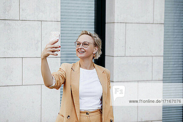 Smiling mature female professional taking selfie through smart phone against wall