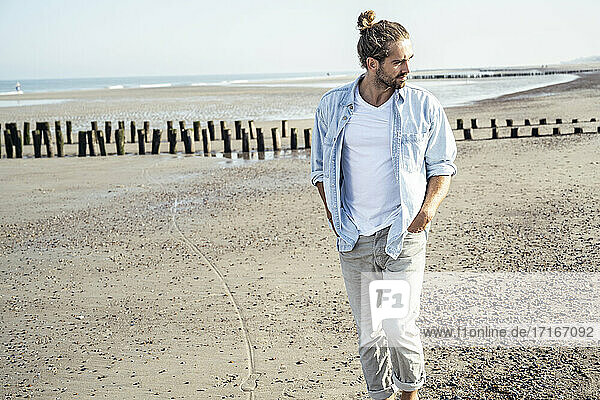 Handsome young man with hands in pockets looking away while walking on beach