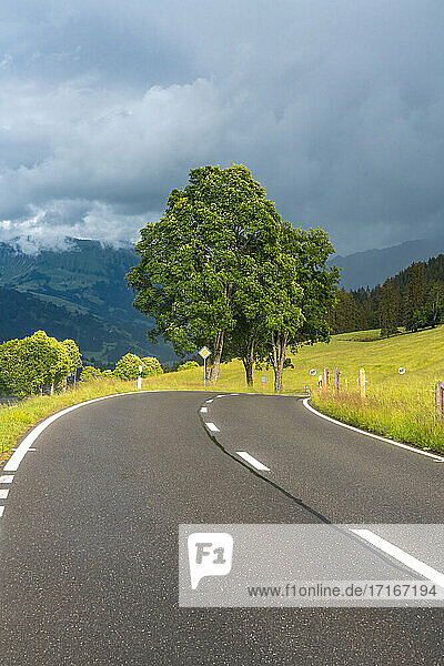Diminishing perspective of mountain road against cloudy sky  Bern  Switzerland