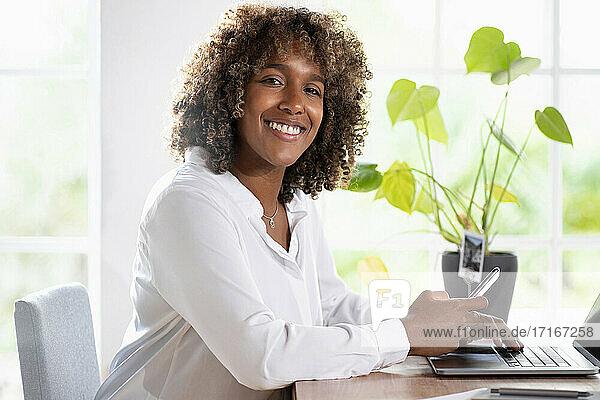 Lächelnder Unternehmer mit Laptop  der ein Mobiltelefon benutzt  während er im Büro zu Hause sitzt Lächelnder Unternehmer mit Laptop, der ein Mobiltelefon benutzt, während er im Büro zu Hause sitzt