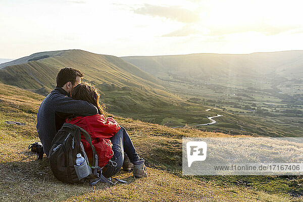 Young couple embracing while looking at sunset during vacations