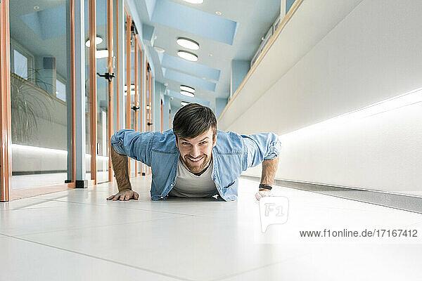 Lächelnder Geschäftsmann macht Liegestütze im Bürokorridor Lächelnder Geschäftsmann macht Liegestütze im Bürokorridor