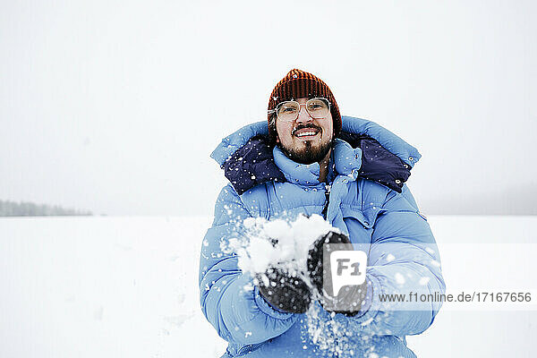 Smiling young man wearing padded jacket while playing on snow