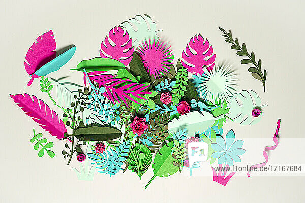 Green and pink paper plants with flowers over white background