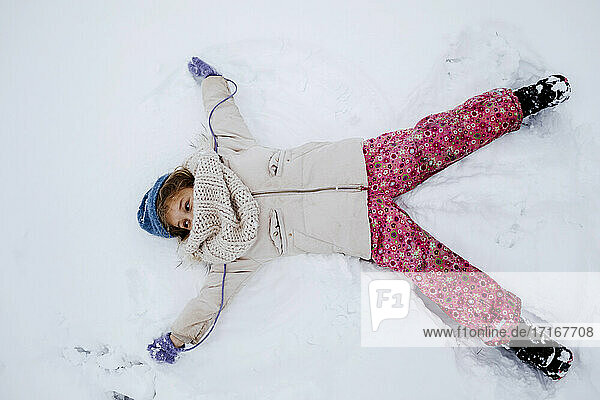 Playful girl making snow angel during winter