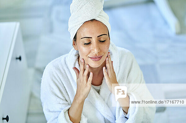Woman in bathrobe massaging her face at home