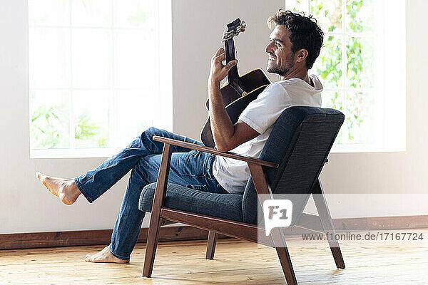 Mittlerer erwachsener Mann lächelt  während er zu Hause Gitarre spielt Mittlerer erwachsener Mann lächelt, während er zu Hause Gitarre spielt