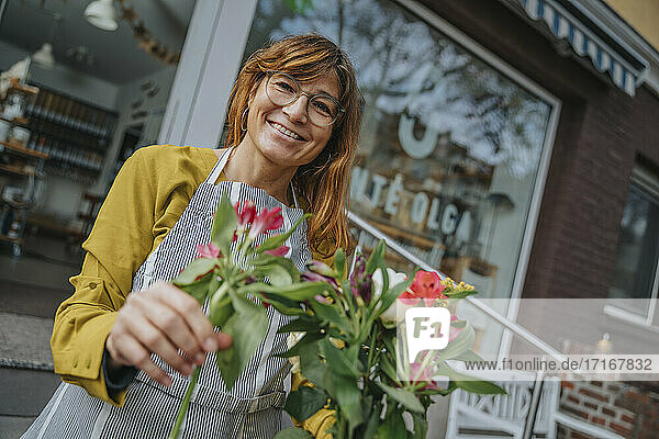 Happy mature female clerk in eyeglasses holding bunch of flowers against organic store