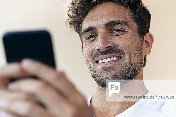 Man smiling while using mobile phone at home