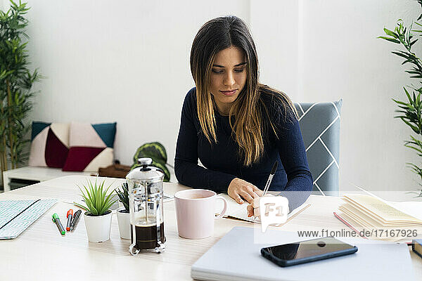 Young female student writing in book while sitting against wall in living room