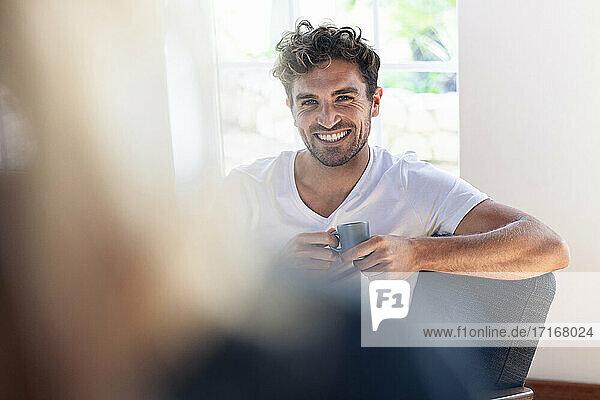 Mann mit Kaffeetasse lächelt  während er eine Frau zu Hause betrachtet Mann mit Kaffeetasse lächelt, während er eine Frau zu Hause betrachtet