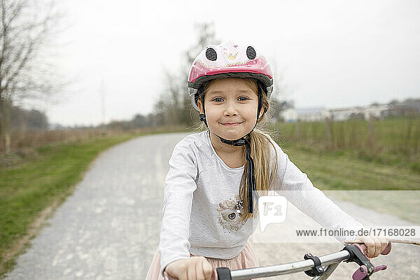 Smiling girl on bicycle wearing cycling helmet
