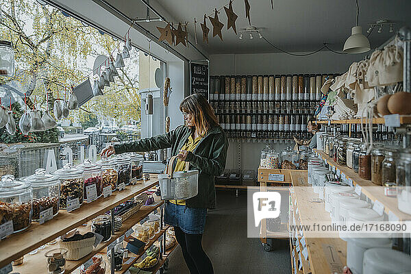 Mature woman shopping groceries from glass jar in zero waste shop