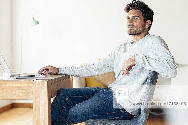 Mann schaut weg,  während er am Tisch im Büro sitzt