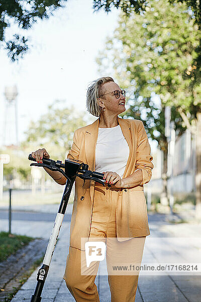 Smiling mature female commuter looking away while standing with electric push scooter on footpath
