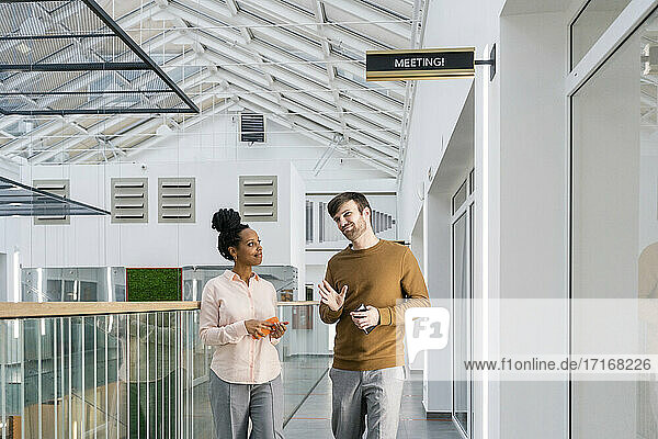 Creative businessman discussing with female colleague while walking in corridor at office