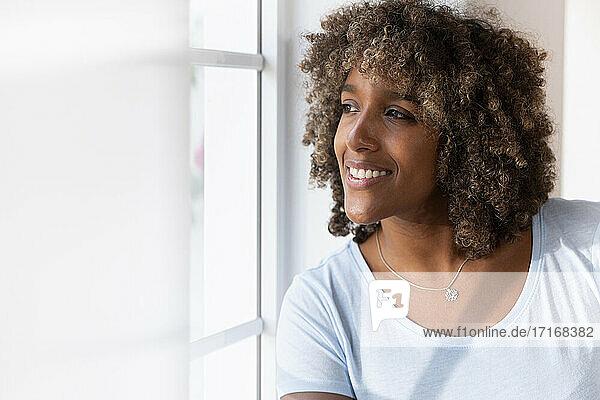 Frau lächelt  während sie durch das Fenster schaut und zu Hause sitzt Frau lächelt, während sie durch das Fenster schaut und zu Hause sitzt