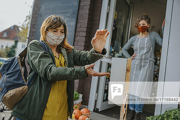 Mature female customer disinfecting hands with sanitizer before entering organic store