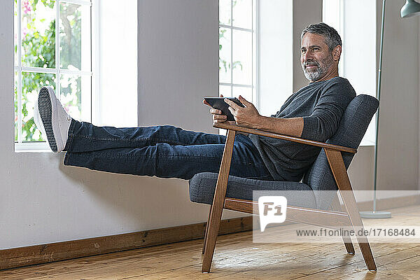 Smiling businessman using digital tablet while sitting on armchair at home