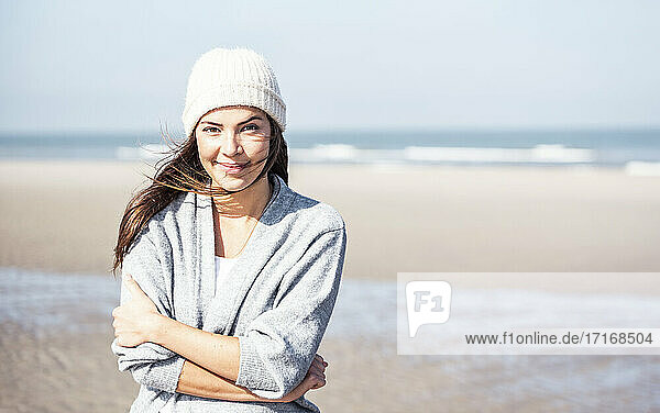 Smiling beautiful woman in cardigan sweater at beach on sunny day