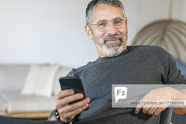Smiling businessman wearing eyeglasses using mobile phone while sitting at home