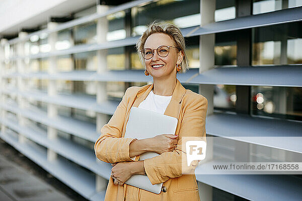 Smiling mature female entrepreneur holding laptop against office building