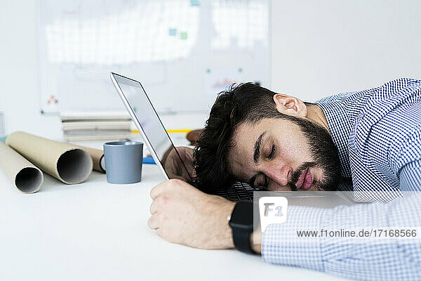 Tired businessman sleeping on laptop in creative office