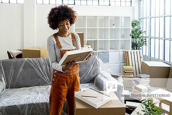 Smiling young woman looking at picture frame while unpacking in new apartment