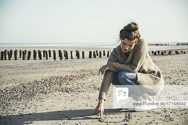 Beautiful woman drawing heart on sand against sky at beach