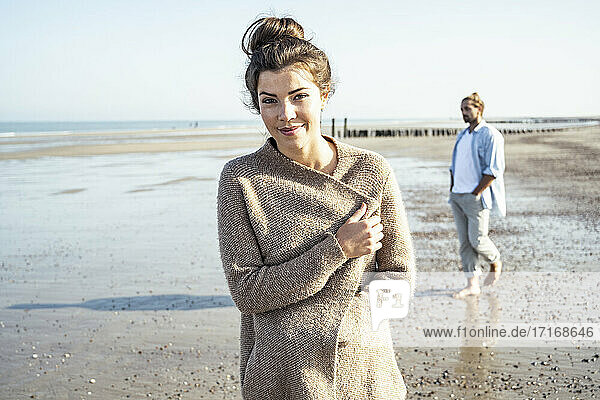 Young woman standing on beach while boyfriend walking in background during weekend