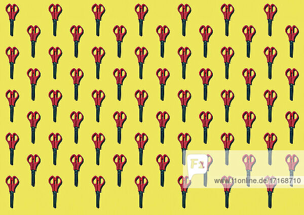 Pattern of rows of scissors against yellow background