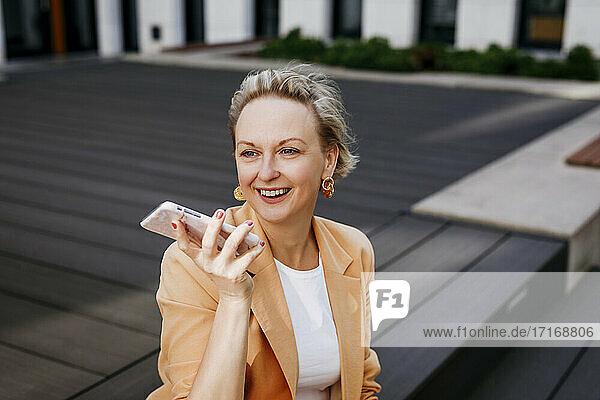Happy female entrepreneur talking through smart phone while sitting on floorboard