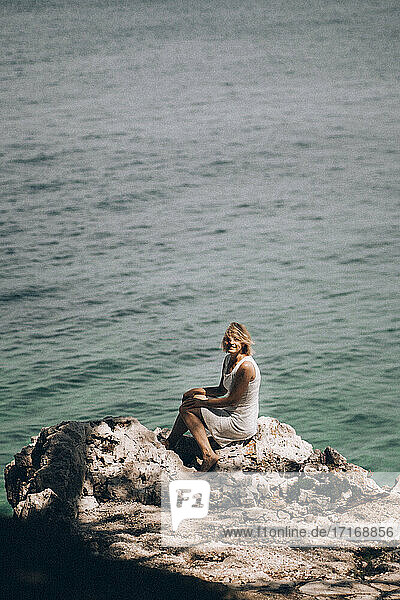 Mature woman sitting on rock at beach against seascape during sunny day