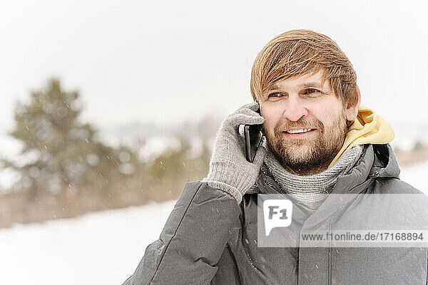 Close-up of smiling mid adult man talking over mobile phone against clear sky