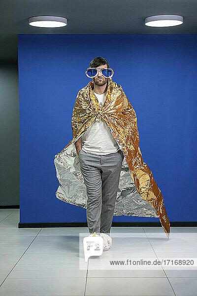 Männlicher Profi mit Händen in den Taschen zu Fuß in Gold Farbe Verpackung Papier Umhang im Büro Männlicher Profi mit Händen in den Taschen zu Fuß in Gold Farbe Verpackung Papier Umhang im Büro