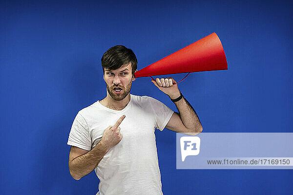 Männlicher Unternehmer  der ein Megaphon an sein Ohr hält und auf eine blaue Wand am Arbeitsplatz zeigt Männlicher Unternehmer, der ein Megaphon an sein Ohr hält und auf eine blaue Wand am Arbeitsplatz zeigt