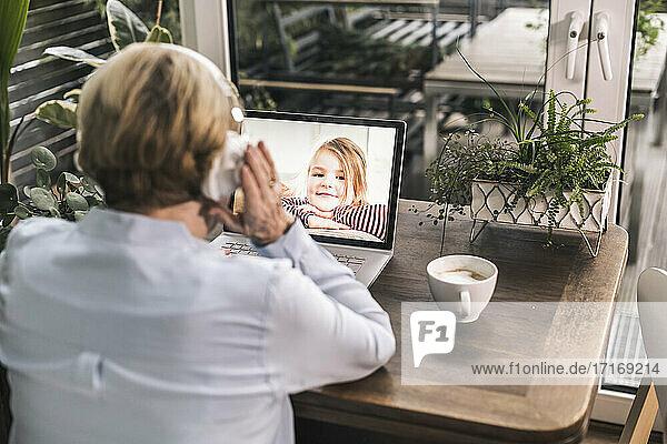 Lächelndes Enkelkind  das über einen Laptop im Wohnzimmer einen Videoanruf mit der Großmutter führt Lächelndes Enkelkind, das über einen Laptop im Wohnzimmer einen Videoanruf mit der Großmutter führt