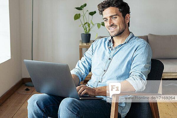 Lächelnder Mann,  der einen Laptop benutzt,  während er zu Hause auf einem Sessel sitzt