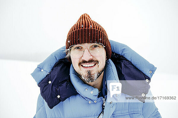 Smiling man with eyeglasses on snow during vacations