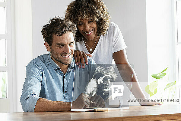 Happy couple checking ultrasound image over transparent screen at home