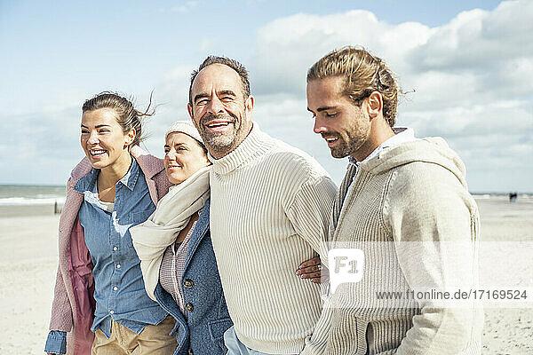 Gruppe erwachsener Freunde  die zusammen am Küstenstrand stehen Gruppe erwachsener Freunde, die zusammen am Küstenstrand stehen
