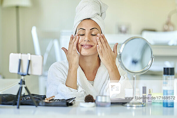 Female influencer applying face cream on her face while blogging through mobile phone at home