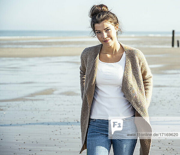 Beautiful woman with hands in pockets walking on beach during sunny day