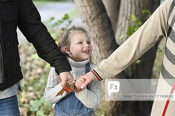 Smiling girl holding mother's and father's hands in park