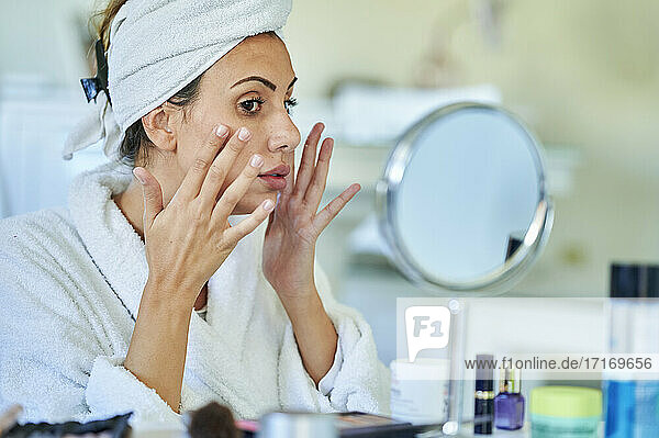 Woman applying cream on her face in front of mirror home
