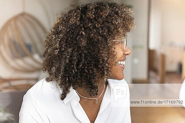 Frau mit lockigem Haar  die wegschaut  während sie zu Hause sitzt Frau mit lockigem Haar, die wegschaut, während sie zu Hause sitzt
