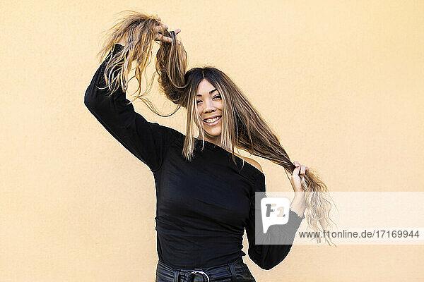 Verspielte junge Frau  die an ihren Haaren zieht  während sie vor einem beigen Hintergrund steht