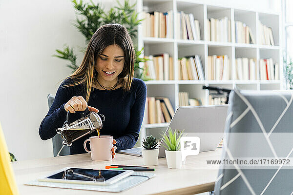 Smiling student pouring black coffee in cup while sitting by laptop in living room